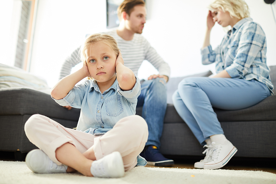couple arguing while child sits on the floor covering her ears
