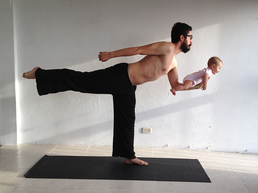 man doing excercise while holding his baby